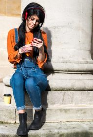 Young woman sitting beside pillar, wearing headphones, holding smartphone